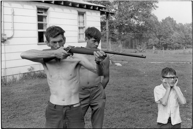 William Gedney - Willie Cornett firing rifle with boys looking on, 1972